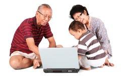 Behandla som ett barn pojken lär hur man använder en bärbar dator Arkivfoto
