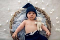 Behandla som ett barn pojken som ligger i en korg med pälshatt-handarbete fotografering för bildbyråer