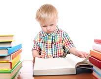 Behandla som ett barn pojken med böckerna Arkivfoto