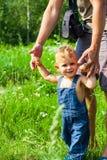 Behandla som ett barn pojken med blåa ögon parkerar in förtroendefamiljhänder av den barnsonen och fadern på den utomhus- fältnat royaltyfri bild