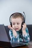 Behandla som ett barn pojken med hörlurar Arkivfoto