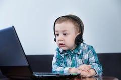 Behandla som ett barn pojken med hörlurar genom att använda datoren Royaltyfri Bild