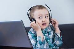 Behandla som ett barn pojken med hörlurar på datoren Royaltyfria Foton