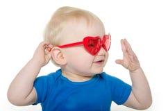 Behandla som ett barn pojken med hjärta formad solglasögon Arkivbild