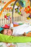 Behandla som ett barn pojken med hängande leksaker Arkivfoto