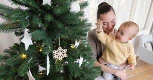 Behandla som ett barn pojken med modern dekorerar julgranen arkivfilmer