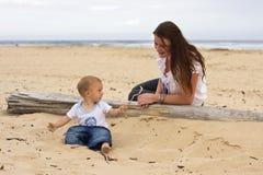 Behandla som ett barn pojken med modern på strand arkivfoto