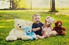 Behandla som ett barn pojken med nallebjörnar Arkivbilder