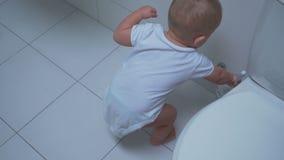 Behandla som ett barn pojken med toalettlokalvårdborsten stock video