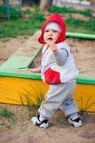 behandla som ett barn pojken nära den leka sandlådan för lekplatsen Fotografering för Bildbyråer