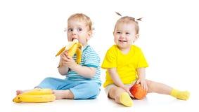 Behandla som ett barn pojken och flickan som äter isolerade frukter Arkivbilder