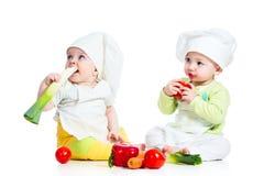 Behandla som ett barn pojken och flickan som ha på sig en kock Arkivfoton