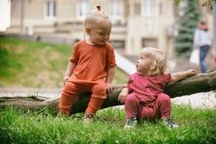 Behandla som ett barn pojken och behandla som ett barn flickan som spelar, medan sitta på grönt gräs Arkivbild