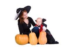 Behandla som ett barn pojken och fostra i den svart halloween kappan Fotografering för Bildbyråer