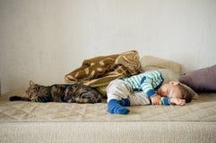 Behandla som ett barn pojken och katten som tillsammans sover Fotografering för Bildbyråer