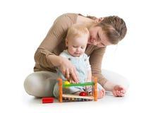 Behandla som ett barn pojken och modern som spelar samman med den logiska leksaken Arkivfoton