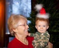 Behandla som ett barn pojken och mormodern med jultomtenhatten Arkivbilder