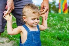 Behandla som ett barn pojken parkerar in Förtroendefamiljhänder av den barnsonen och fadern arkivbilder