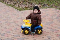 Behandla som ett barn pojken som rider en leksakbil Royaltyfri Bild