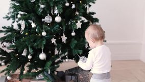 Behandla som ett barn pojken som ser leksaker på julgranen arkivfilmer