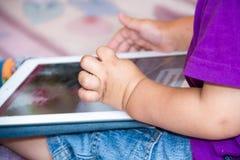 Behandla som ett barn pojken sitter på golvet som spelar med minnestavlaPC Närbildfoto av händerna Litet handlagblock som lär tid royaltyfria bilder