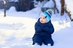 Behandla som ett barn pojken som sitter på snö royaltyfria bilder