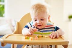 Behandla som ett barn pojken som äter frukt i hög stol Royaltyfri Bild