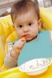 Behandla som ett barn pojken som äter i kickstol Arkivbild