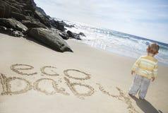 Behandla som ett barn pojken som anseendet vid Eco behandla som ett barn skriftligt på sand Royaltyfri Fotografi