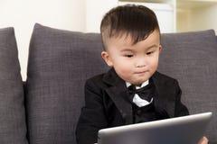 Behandla som ett barn pojken som använder den digitala minnestavlan Royaltyfri Bild