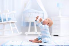 Behandla som ett barn pojken som att dricka mjölkar i solig barnkammare royaltyfria foton