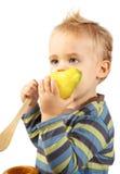 behandla som ett barn pojken som äter pearen Royaltyfri Foto