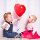 Behandla som ett barn pojken som ger en hjärtaballong till flickan Fotografering för Bildbyråer