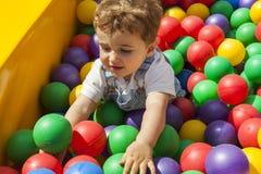 Behandla som ett barn pojken som har gyckel som spelar i en färgrik plast- bollpöl Arkivfoton