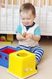 Behandla som ett barn pojken som hemma spelar leksaker Royaltyfri Foto