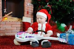 Behandla som ett barn pojken som kläs som Santa Claus sammanträde med en gitarr i hans han Royaltyfri Foto