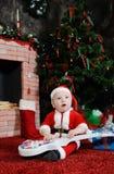 Behandla som ett barn pojken som kläs som Santa Claus sammanträde med en gitarr i hans han Royaltyfria Bilder