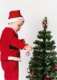 Behandla som ett barn pojken som kläs som Santa Claus som dekorerar julgranen. royaltyfri fotografi