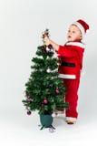 Behandla som ett barn pojken som kläs som Santa Claus som dekorerar julgranen, hängning royaltyfri bild