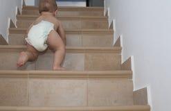 Behandla som ett barn pojken som kryper upp trappan Royaltyfri Bild
