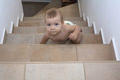 Behandla som ett barn pojken som kryper upp trappan Arkivfoton