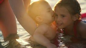 Behandla som ett barn pojken som kyssar behandla som ett barn flickan på havet arkivfilmer