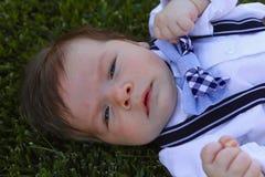 Behandla som ett barn pojken som lägger i gräs Arkivfoto