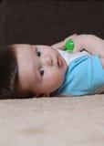 Behandla som ett barn pojken som ligger på golvet som ser till kameran royaltyfria foton