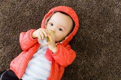 Behandla som ett barn pojken som matar med, mjölkar botten Arkivbild