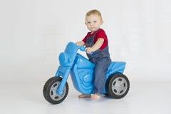 Behandla som ett barn pojken som rider hans plast- sparkcykel Royaltyfri Fotografi