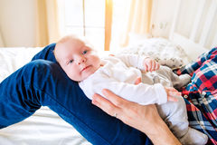 Behandla som ett barn pojken som rymms av hans fadersammanträde på säng Royaltyfri Foto