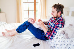 Behandla som ett barn pojken som rymms av hans fadersammanträde på säng Arkivbilder