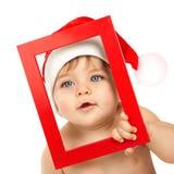 Behandla som ett barn pojken som slitage den Santa Claus hatten Arkivbild
