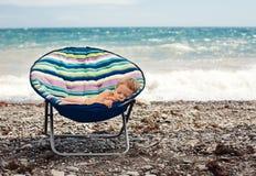 Behandla som ett barn pojken som sovar på stranden Royaltyfria Foton